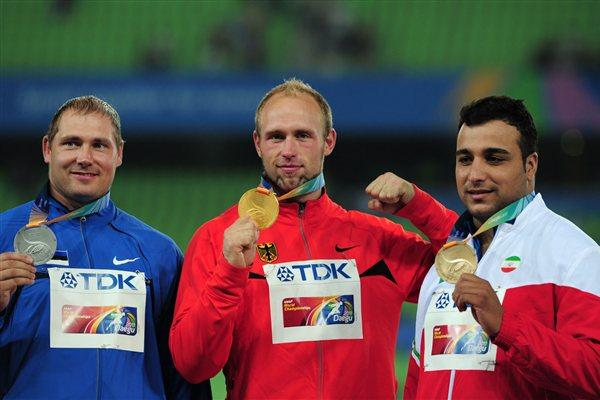 Robert Harting of Germany poses with the gold medal after his victory in the Men's discus final with Gerd Kanter of Estonia (L) and Ehsan Hadadi of Iran (R)  (Getty Images)