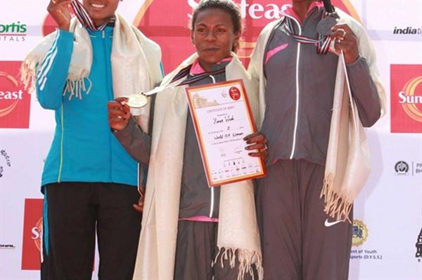 Sunfeast 10K women's podium: from left: runner up Aselefech Mergia, winner Ayalew Wude Yimer, and Grace Momanyi (organisers)