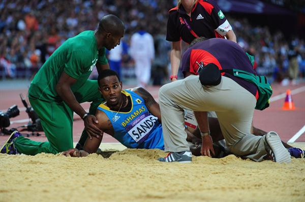 Leevan Sands of the Bahamas gets assisted off the sand after getting injured in the Men's Triple Jump Final of the London 2012 Olympic Games on 9 August 2012 (Getty Images)