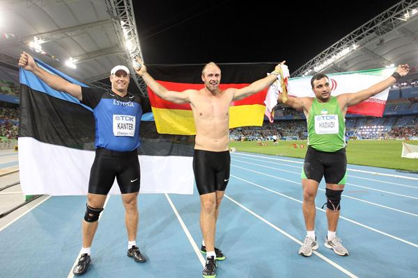 Robert Harting of Germany celebrates victory in the Men's discus final with Gerd Kanter of Estonia (L) and Ehsan Hadadi of Iran (R) during day four  (Getty Images)