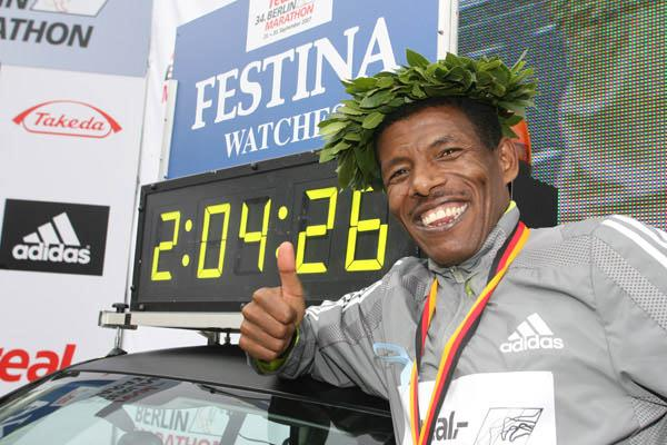 The smile says it all - Haile Gebrselassie next to his World record clock in Berlin (Victah Sailer)