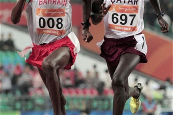 Bilisuma Shugi Gelassa (left) powers away from Qatari Essa Ismal Rashed in the 10,000m at the 2010 Asian Games (Getty Images)