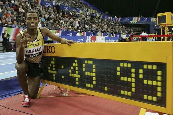 A familiar pose - Kenenisa Bekele next the clock after his 2000m world best (Getty Images)