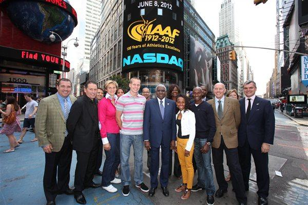 In front in NASDAQ headquarters in Times Square with the IAAF Centenary logo on the NASDAQ giant screen. First row from left: Mark Wetmore, Ian Stewart, Barbora Spotakova, Jesse Williams, Lamine Diack, Meseret Defar, Bernard Lagat, Steve Ovett, and Nick Davies (NASDAQ)