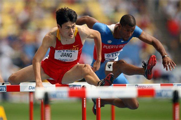 Fan Jiang (L) of China and Hector Cotto of Puerto Rico compete in the men's 110 metres hurdles heats (Getty Images)