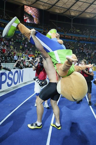 Berlino the Bear is thrown over the shoulder of the newly crowned men's Discus Champion Robert Harting during his celebrations at the 12th IAAF World Championships in Athletics in Berlin (Getty Images)