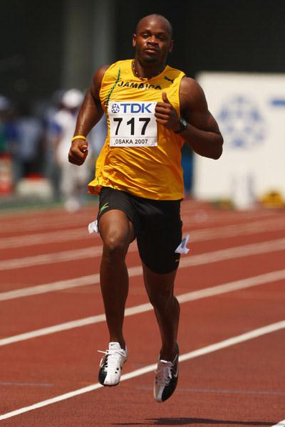 Asafa Powell jogging through the heat in the 100m first round (Getty Images)