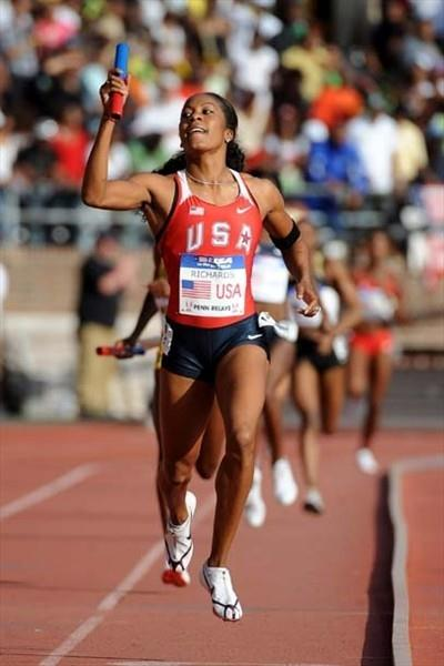 Sanya Richards raises arm in triumph after bringing USA 'RED' home at Penn Relays (Kirby Lee)
