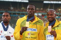 The medallists from the men's 100m final (L-R) USA's Tyson Gay receives the silver, Usain Bolt the gold medal plus World Record and his compatriot Asafa Powell the bronze medal (Getty Images)