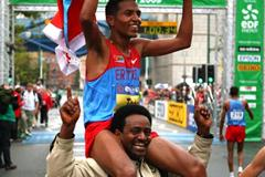 Zersenay Tadese celebrates with an Eritrean supporter after winning the IAAF/EDF Energy World Half Marathon Championships in Birmingham (Getty Images)