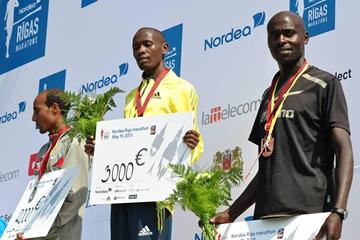Duncan Koech (centre) with his winner's cheque after the Nordea Riga Marathon (organisers)
