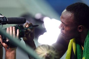 Usain Bolt of Jamaica signs a camera lens after winning the gold medal in the men's 4x100m at the 12th IAAF World Championships in Athletics (Getty Images)