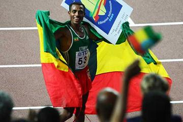 Bekele with a banner displaying the celebration of the Ethiopian Millennium 2000 - based upon their unique calendar - acknowledges his fans in Osaka (Getty Images)