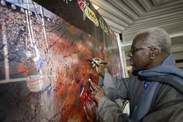 Lamine Diack signs the Outreach athletes' board in the village (Hannu Jukola)