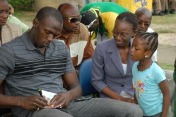 Usain Bolt signing autographs for young fans in Trelawny (Paul Reid)