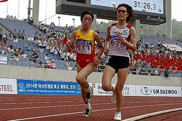 Asian Champs women's 10,000m: Winner Bai Xue (l) passes silver medallist Yumi Sato of Japan (r) (c)