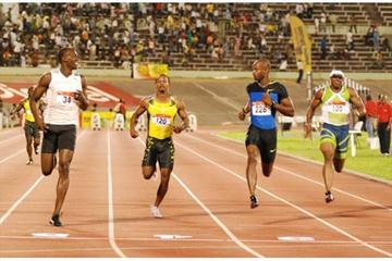 Usain Bolt (left) cruises across the finish line to win the men's 100m dash at Saturday's Jamaica's Olympic Trials. Asafa Powell (second right) was second ahead of Michael Frater (Sporting Eagle)
