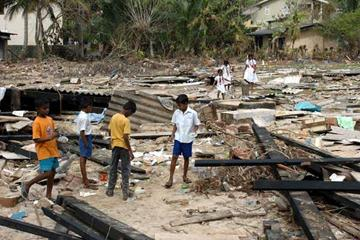 Sri Lankan school children walk amid debris lying in the devastated courtyard of their school (AFP/Getty Images)
