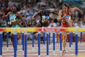 Priscilla Lopes-Schliep of Canada (right) and Damu Cherry of the USA (centre) qualify for the 100m hurdles semi finals (Getty Images)