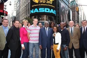 In front in NASDAQ headquarters in Times Square with the IAAF Centenary logo on the NASDAQ giant screen. First row from left: Mark Wetmore, Ian Stewart, Barbora Spotakova, Jesse Williams, Lamine Diack, Meseret Defar, Bernard Lagat, Steve Ovett, and Nick Davies (NASDAQ)