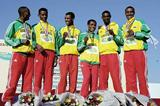 A smiling Bekele with short race gold medal team members (Getty Images)