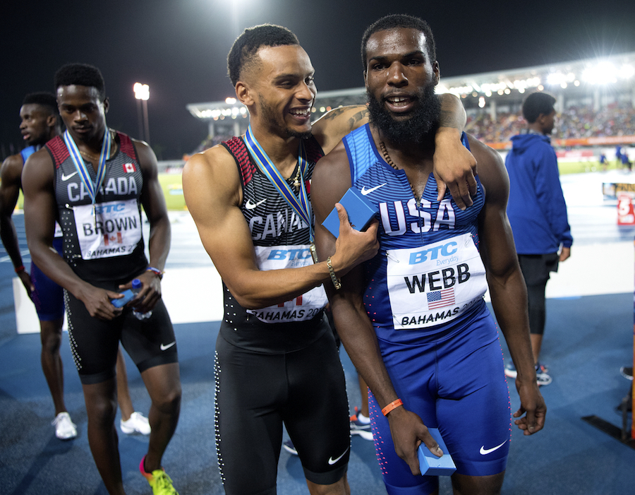 Andre De Grasse and Ameer Webb hug after the men's 4x200m final by Jeff Cohen