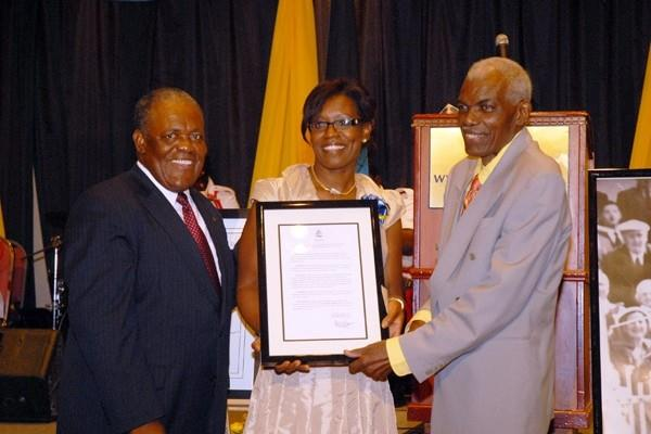 Thomas Augustus (Tommy) Robinson (r) being presented with a framed copy of the  Prime Minister Hubert Ingraham's Proclamation declaring Friday, 24 July as 'Tommy Robinson Day'. Committee Member Sandra Smith (middle) (David Charlton)