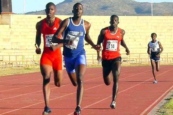 Botswana's Zacharia Kamberuka (in Blue kit) leads Zimbabwe's Nelson Ndebele (in All red) and Zambia Quincy Mutale (no 114) and Namibia athlete (in far distance) on the second leg of the 4x400m. Botswana eventually won in a photo finish. (Mark Ouma)