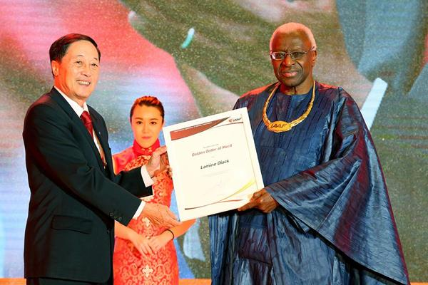 Former IAAF Vice President  Lou Dapeng presents IAAF President Lamine Diack with the IAAF Golden Order of Merit at the Opening Ceremony and Dinner for the 50th IAAF Congress at the Great Hall of the People in Beijing (Getty Images)