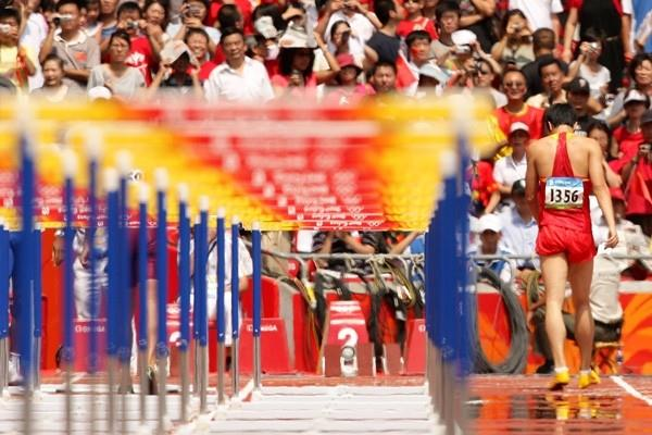 Liu Xiang walks off the track injured (Getty Images)