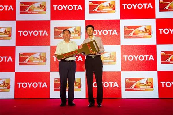 Toyota Motor China executive vice president Dong Changzheng hands the key to Chen Jie, executive secretary of the local organising committee (Toyota / Beijing 2015 LOC)