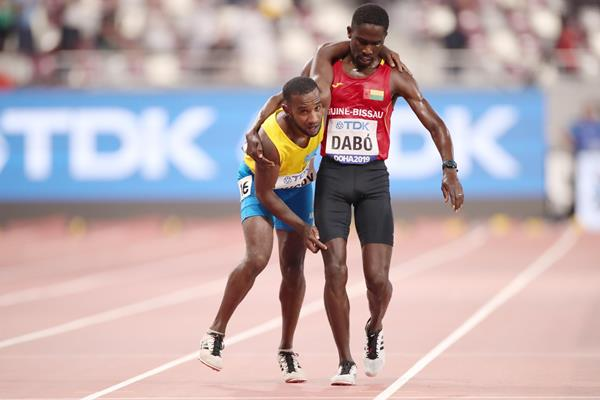 Braima Suncar Dabo (r) helping Jonathan Busby of Aruba to the finish of the their heat in the 5000m at the IAAF World Athletics Championships Doha 2019 (Getty Images)