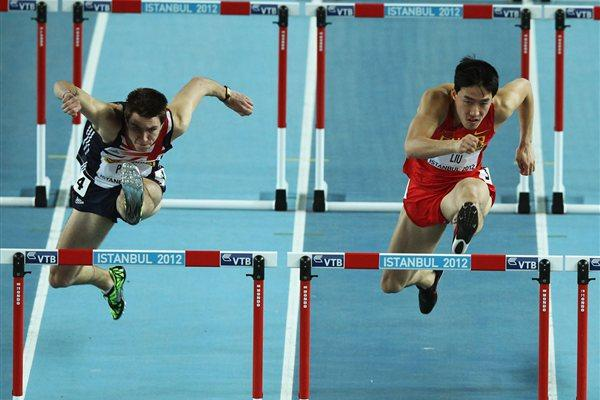 Andrew Pozzi of Great Britain and Lui Xiang of China compete in the Men's 60 Metres Hurdles first round during day two - WIC Istanbul (Getty Images)