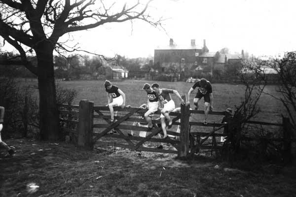 March 1913: Competitors in the English National Cross Country Championships climbing over a gate on the route (Topical Press Agency/Getty Images)