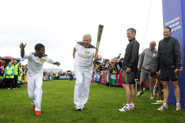 Brendan Foster and Haile Gebrselassie cross the Great North Run finish line with the Olympic flame during the 2012 torch relay (Getty Images)