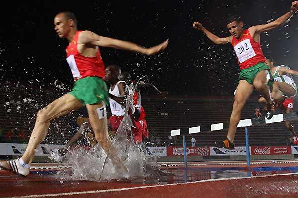 Moroccan 3000m Steeplechase gold medallist Abulqader el-Hashlaf (L) powers through the water with Moroccan silver medal winner Hamid el-Zein (R) at the 11th Pan Arab Games in Cairo, 23 November 2007 (AFP / Getty Images)