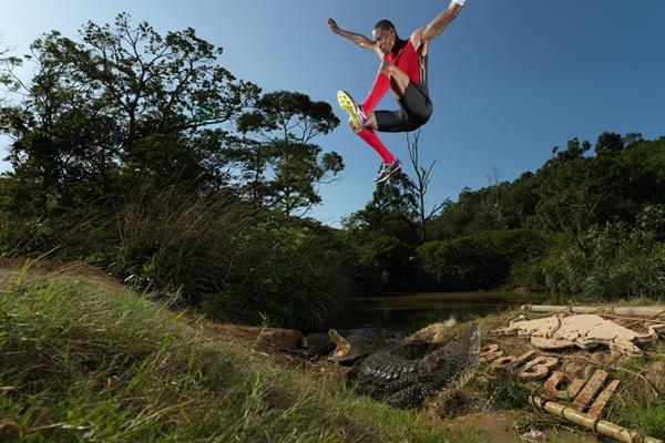 A crocodile looks up as Godfrey Mokoena sails through the air above it (Red Bull)