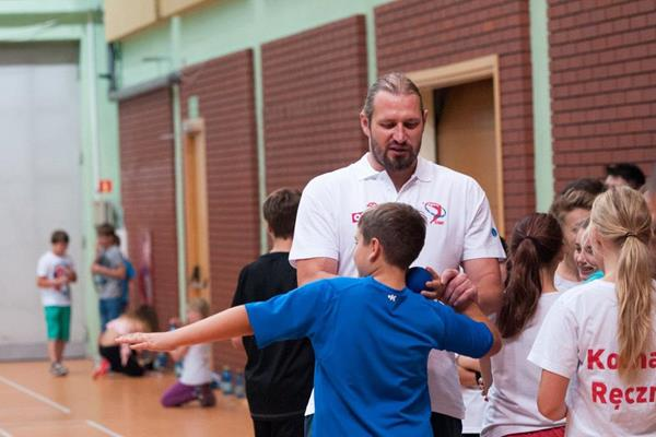 Tomasz Majewski instructs a child how to putt the shot (Organisers)