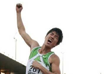 Liu Xiang celebrates while sitting on his World record clock in Lausanne (AFP / Getty Images)