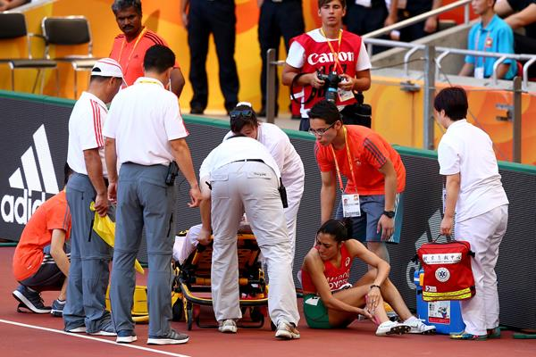 Siham Hilali is given assistance after pulling up injured in the 1500m heats at the IAAF World Championships, Beijing 2015 (Getty Images)