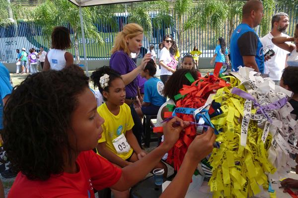 Children writing their hopes and dreams on ribbons an attaching them to the Nanairo tree during the Ekiden Project Rio 2016 (IAAF)