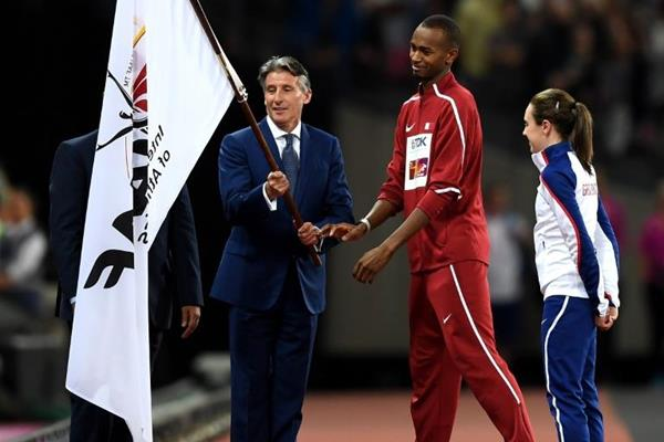 IAAF President Sebastian Coe hands the IAAF flag to Mutaz Essa Barshim of Qatar, the host nation of the next IAAF World Championships (Getty Images)