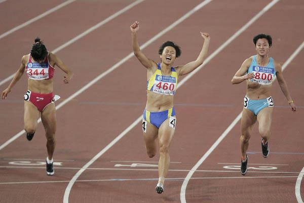 Qin Wangping celebrates after winning the 100 metres at 10th National Games (Getty Images)