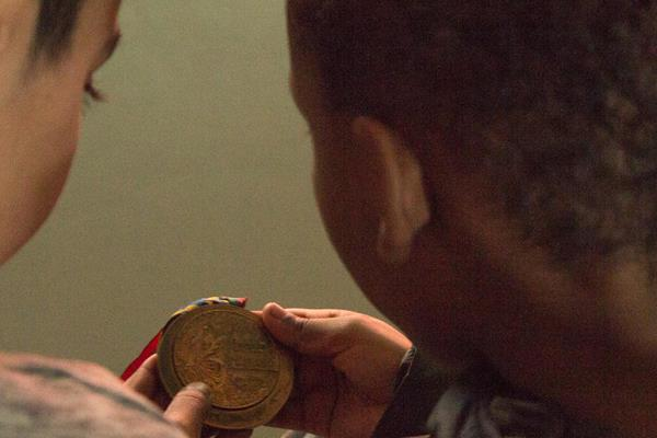 Primary school students at the Aby Skole school in Aarhus, Denmark look at one of Lynn Jennings' world cross country championships gold medals (Bob Ramsak)