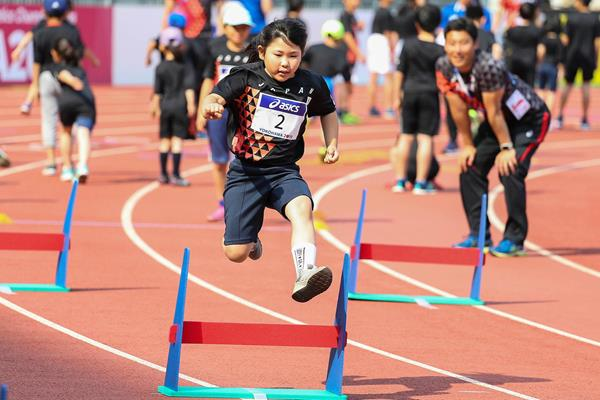 A school girl jumps over a hurdle at the Asics Kids Decathlon Challenge in Yokohama (Roger Sedres)