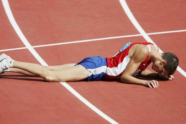 Denis Nizhegorodov of Russia collapses to the floor after taking silver in the 50km walk (Getty Images)