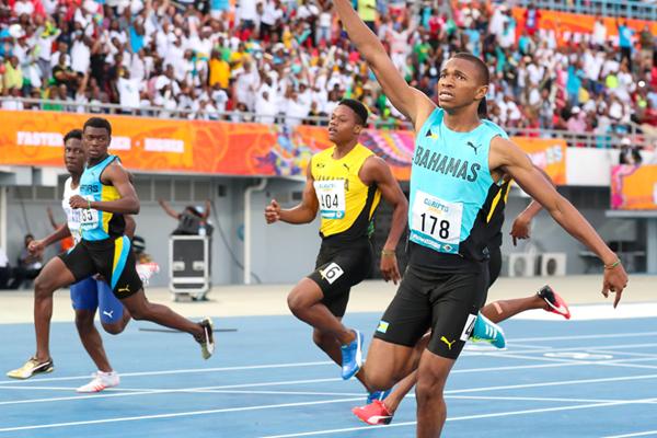Joel Johnson wins the 100m at the Carifta Games (Leo Hudson)