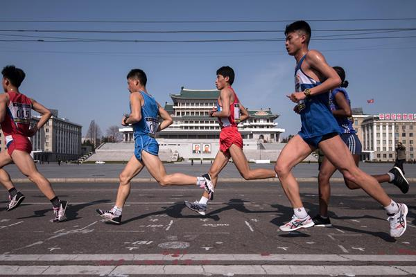 Competitors run through Kim Il-Sung square during the Pyongyang Marathon (AFP)