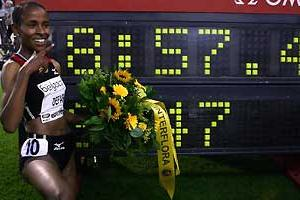 Defar kneels in Brussels next to the clock displaying her World best for Two Miles (Getty Images)