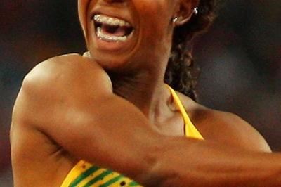 Shelly-Ann Fraser jumps over the finish line in celebration of her 100m victory (Getty Images)